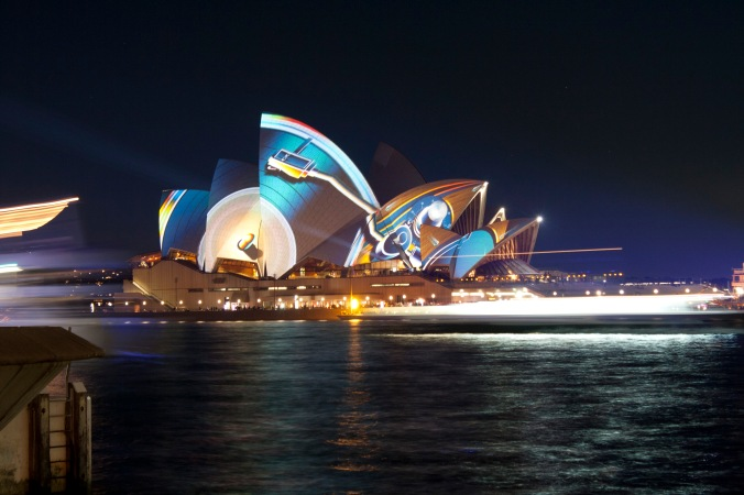 Ferries passing in the night with the Opera House in the background.